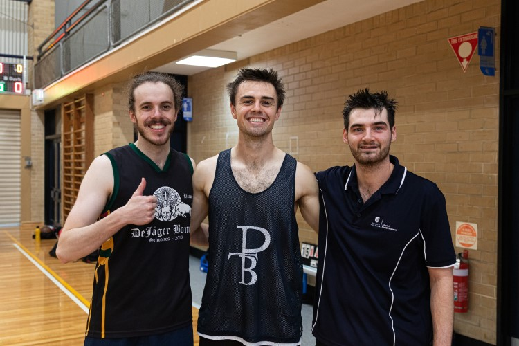 Three teammates smile at the camera